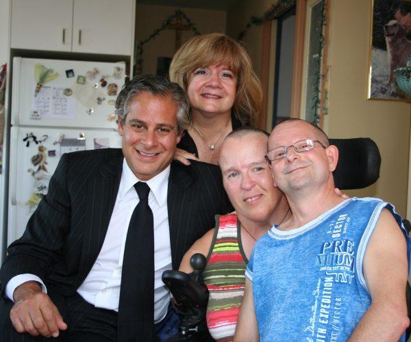 Stephen Raynes et Mercedes Benegbi, accompagnés d'une survivante de la thalidomide et de son conjoint. Photo prise dans une cuisine de maison.