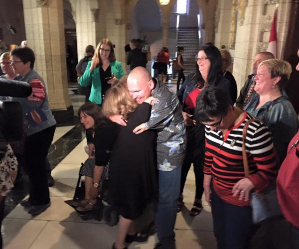 Deux survivants de la thalidomide enlacés encerclés de personnes réjouies lors d'une conférence de presse au Parlement du Canada