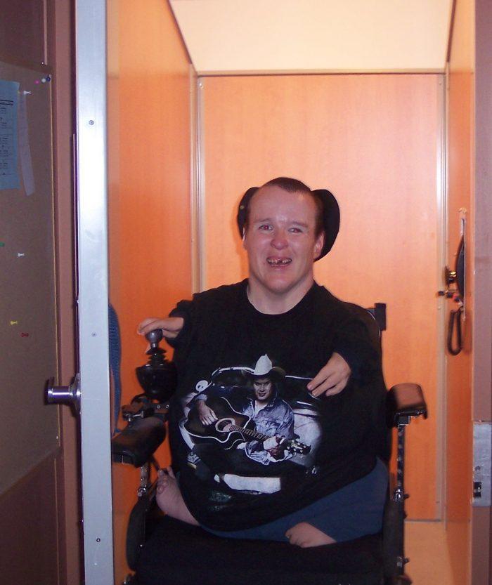 Femme en fauteuil roulant ayant des bras raccourcis et n'ayant pas de jambes sortant d'un ascenseur en souriant.