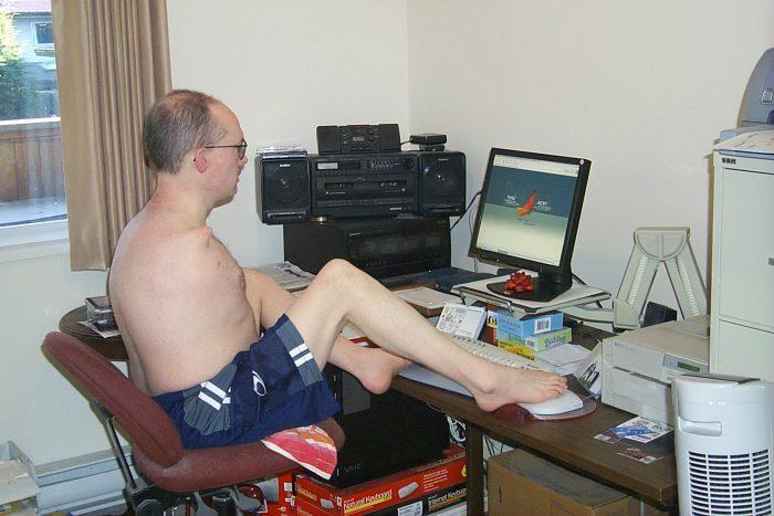 Homme n'ayant pas de bras utilisant un ordinateur avec ses pieds.
